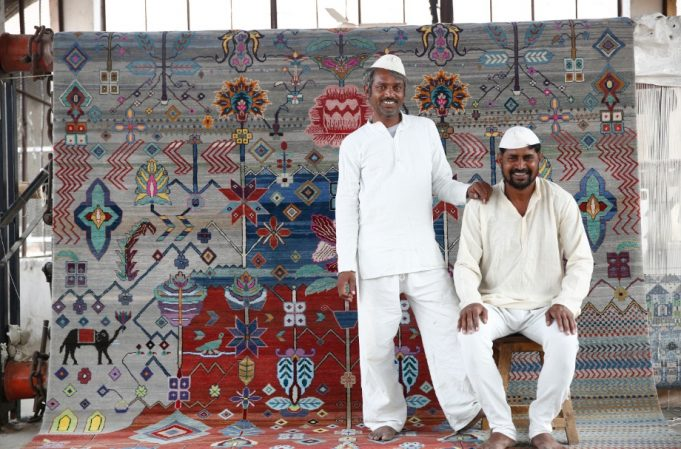 Prison inmates posing with their rug created for Jaipur Rugs' limited-edition collection called Freedom Manchaha